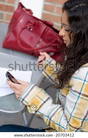 An attractive Indian woman texting or searching the web on her cell phone while seated at a table outdoors. - stock photo