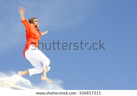 An attractive looking middle aged woman is jumping cheerful and with a happy expression down a sand dune, isolated with clear blue sky as background and copy space. - stock photo