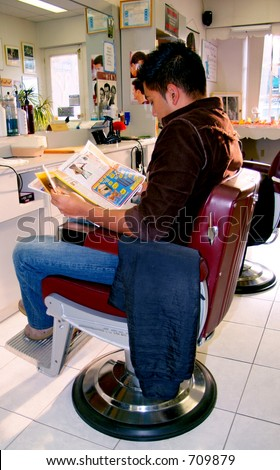 An attractive male looking through a magazine at a local barber shop.