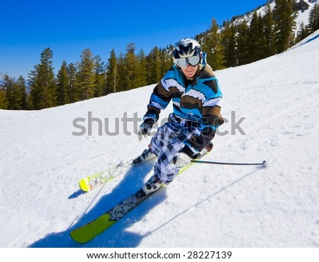 An Attractive Male Skier Rides down the Slope on A Sunny Blue Sky Day - stock photo