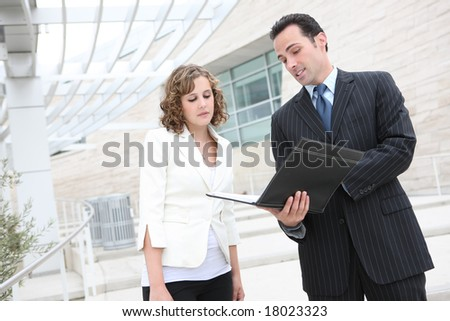 An attractive man and woman business team outside office building