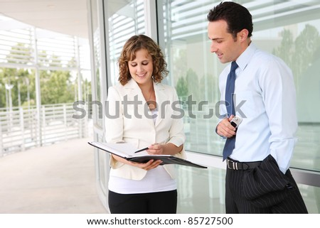 An attractive man and woman business team outside office building - stock photo