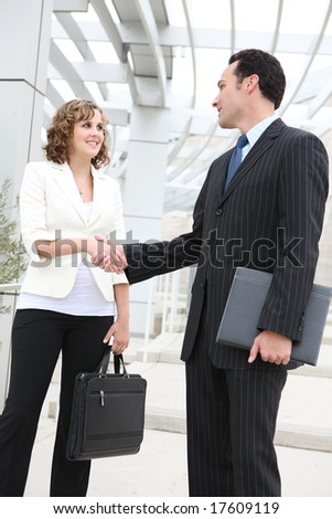 An attractive man and woman business team shaking hands at office
