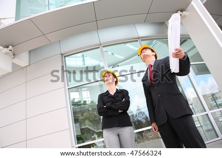 An attractive man and woman business team working construction on the building site - stock photo