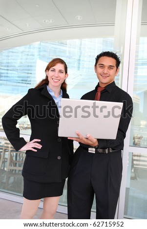 An attractive man and woman business team working on laptop computer outside office - stock photo