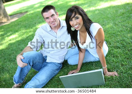 An attractive man and woman couple in the park with a laptop computer