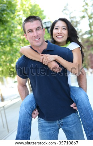 An Attractive man and woman Interracial couple in love  (Focus on Man) - stock photo