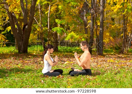 An attractive  man and woman practice Yoga padmasana pose in forest - stock photo