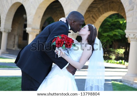 An attractive man and woman wedding couple kissing outside church - stock photo