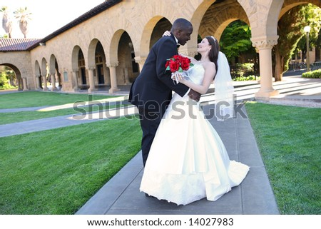 An attractive man and woman wedding couple outside church - stock photo
