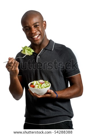 An attractive man eating a salad against white background - stock photo