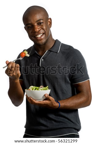 An attractive man eating a salad against white background