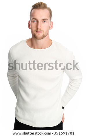 An attractive man in his 20s wearing a white sweater standing against a white background smiling against camera. - stock photo