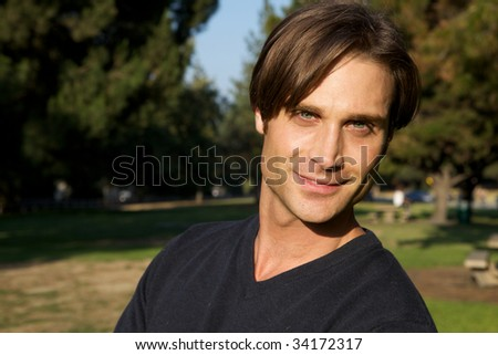 An attractive man in the park with trees - stock photo