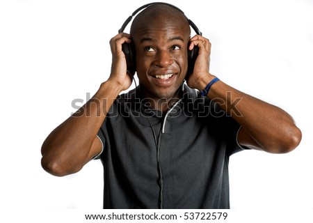 An attractive man listening to music on his headphones against white background - stock photo