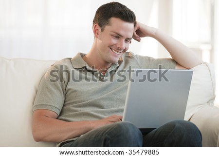 An attractive man sitting on a couch and using a laptop. He is smiling.  Horizontally framed shot.