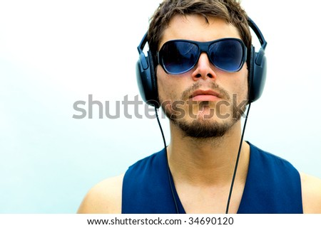 An attractive man with headphones and a blue vest - stock photo