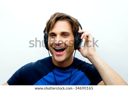 An attractive man with headphones and a blue vest