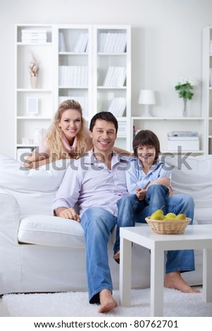 An attractive mature family with a child at home - stock photo