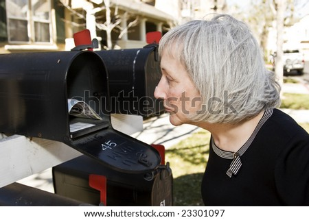 An attractive mature woman is concerned with what she sees inside her mailbox - stock photo