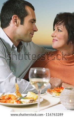 An attractive middle-aged man stares deeply into his partner's eyes over a romantic seafood dinner for two - stock photo