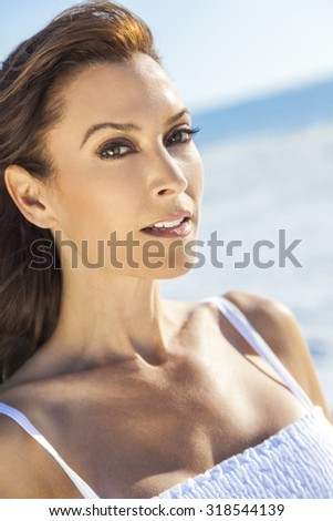 An attractive middle aged woman in her thirties or forties enjoying the sunshine on a beautiful tropical beach