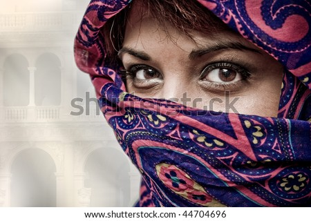 An attractive middle eastern woman wearing a colorful head covering. - stock photo