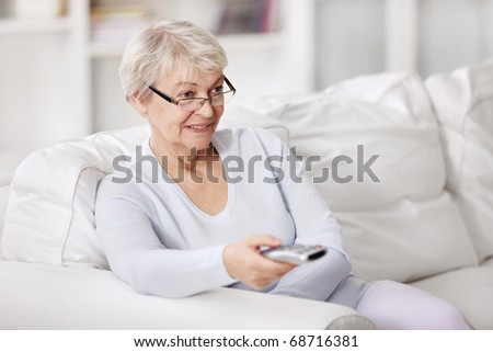 An attractive older woman switches TV channels - stock photo
