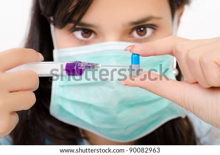 An attractive pharmacist woman inject a liquid in a pill - stock photo