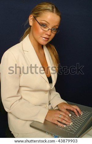 An attractive secretary works on a laptop - stock photo