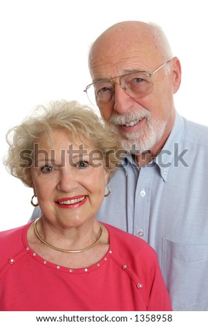 An attractive senior couple against a white background.  Vertical orientation. - stock photo