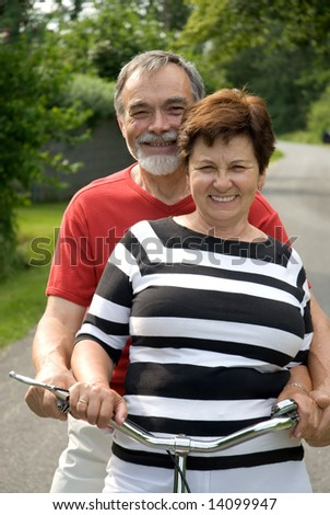 An attractive senior couple bicycling