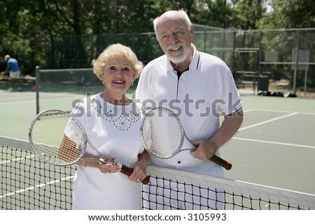 An attractive senior couple ready to play tennis. - stock photo