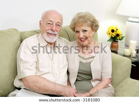 An attractive senior couple relaxing on the couch together. - stock photo