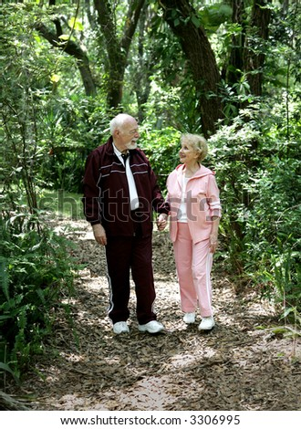 An attractive senior couple strolling through the park hand in hand.