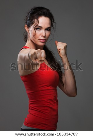 An attractive sexy woman throwing a punch during boxing exercise - stock photo