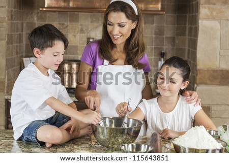 An attractive smiling family of mother and two children, girl boy, son daughter, baking in a kitchen at home - stock photo
