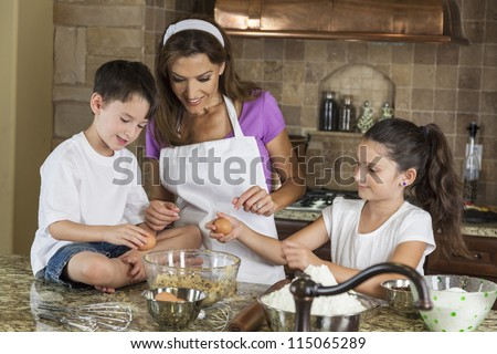 An attractive smiling family of mother, two children, girl, boy, son & daughter, breaking eggs & baking in a kitchen at home - stock photo