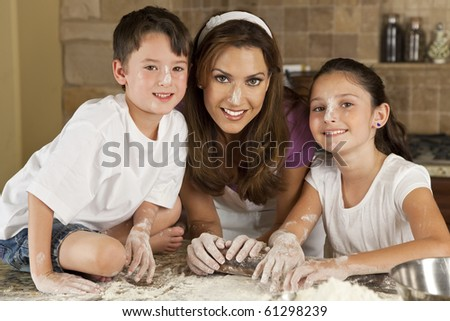 An attractive smiling mother, son and daughter family cooking and baking with flour and a rolling pin in a kitchen at home - stock photo