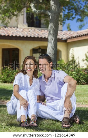 An attractive, successful and happy middle aged man and woman couple in their forties, sitting together outside under a tree and smiling. - stock photo