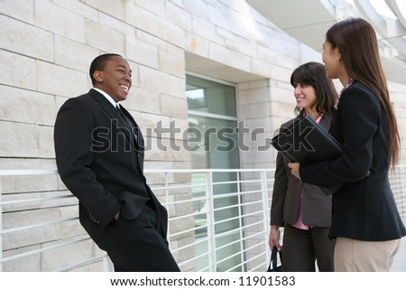 An attractive team of diverse business people talking at company - stock photo