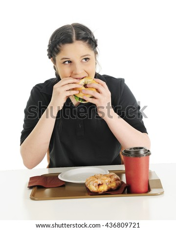 An attractive teen girl biting into a breakfast bagel sandwich.  Her fast food try also contains a coffee mug and glazed fritter.  On a white background.