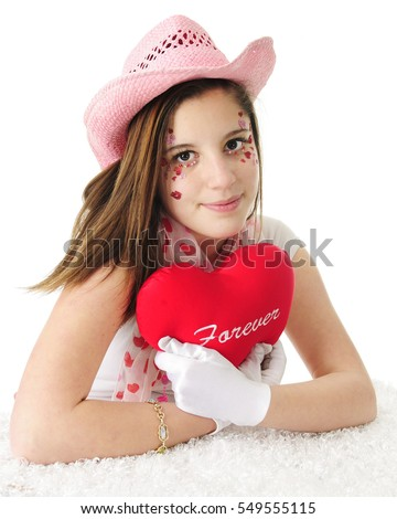"An attractive teen girl in a pink cowgirl hat, her face adorned with sparkly hearts and hugging a ""forever"" heart pillow.  On a white background."