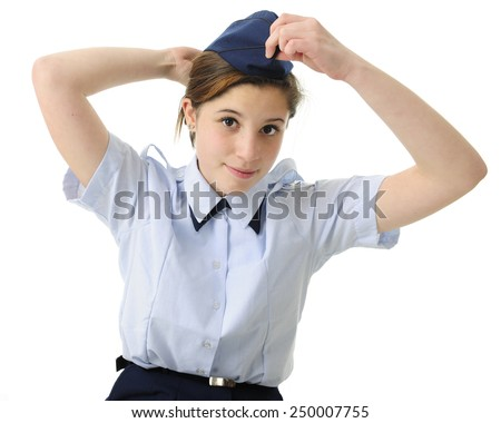 An attractive teen girl putting on her navy blue ROTC hat.  On a white background. - stock photo