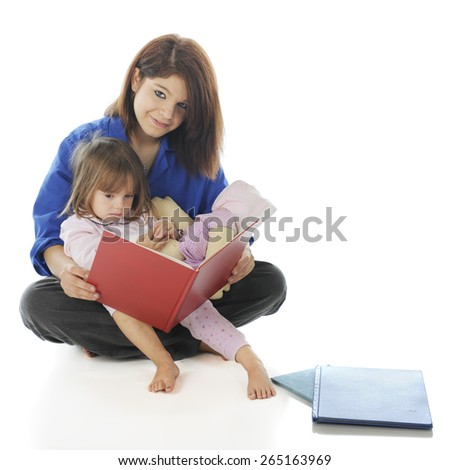 An attractive teen volunteer reading a book to a sad little girl.  On a white background. - stock photo