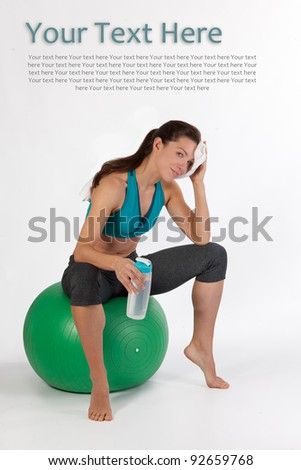 An attractive thin young woman wipes sweat from her forehead while resting on a fit ball and drinking water from a bottle - stock photo
