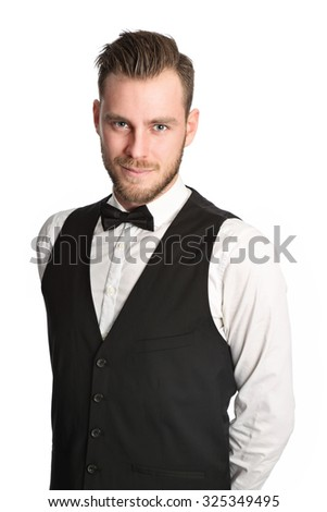 An attractive waiter standing against a white background wearing a black vest, bow tie and a white shirt. - stock photo