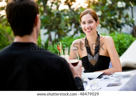 An attractive well-dressed couple having a formal meal outdoors - stock photo