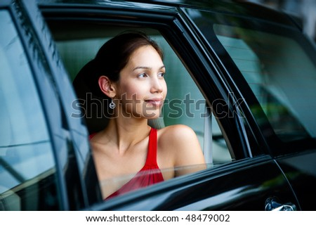 An attractive well-dressed lady looking out a car window - stock photo