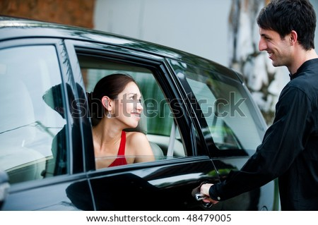 An attractive well-dressed man opening a car door for his partner outdoors - stock photo